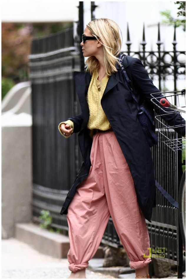 Ashley Olsen in a pair of loose Yoga harem pants and a yellow top with a black coat over it