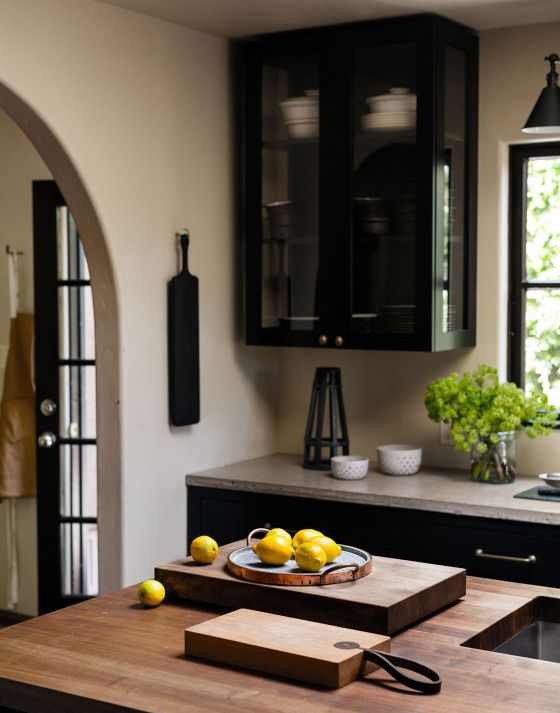 Arched openings, shaker inspired cabinet style, concrete counter, warm wood island counter with stainless sink. California Spanish Revival home, kitchen remodel.