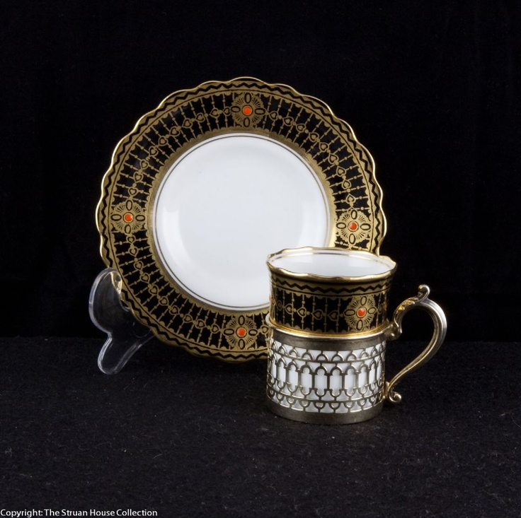 This beautiful black white and gilded Aynsley coffee cup and saucer is held in a perfectly designed silver holder hall marked Birmingham 1931