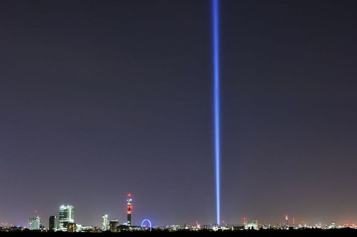 A single beam of light pierces the sky above the houses of parliament. | Spine-Tingling Photos Of London As It Remembers World War I