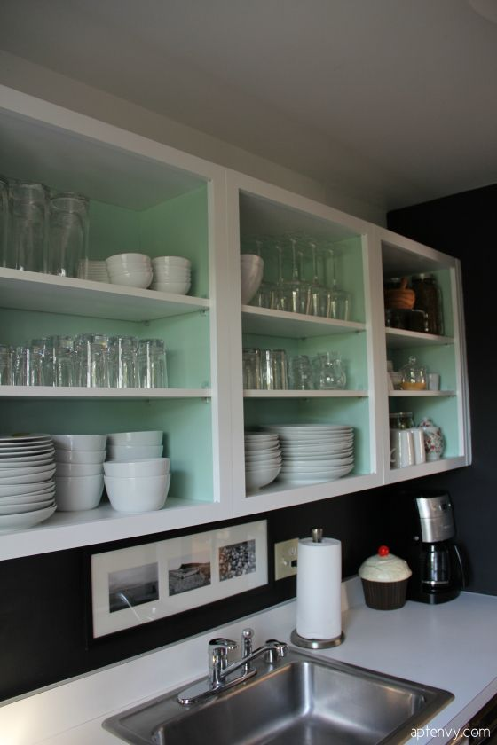White cabinet with pastel inside - maybe jadeite color to match hardware.