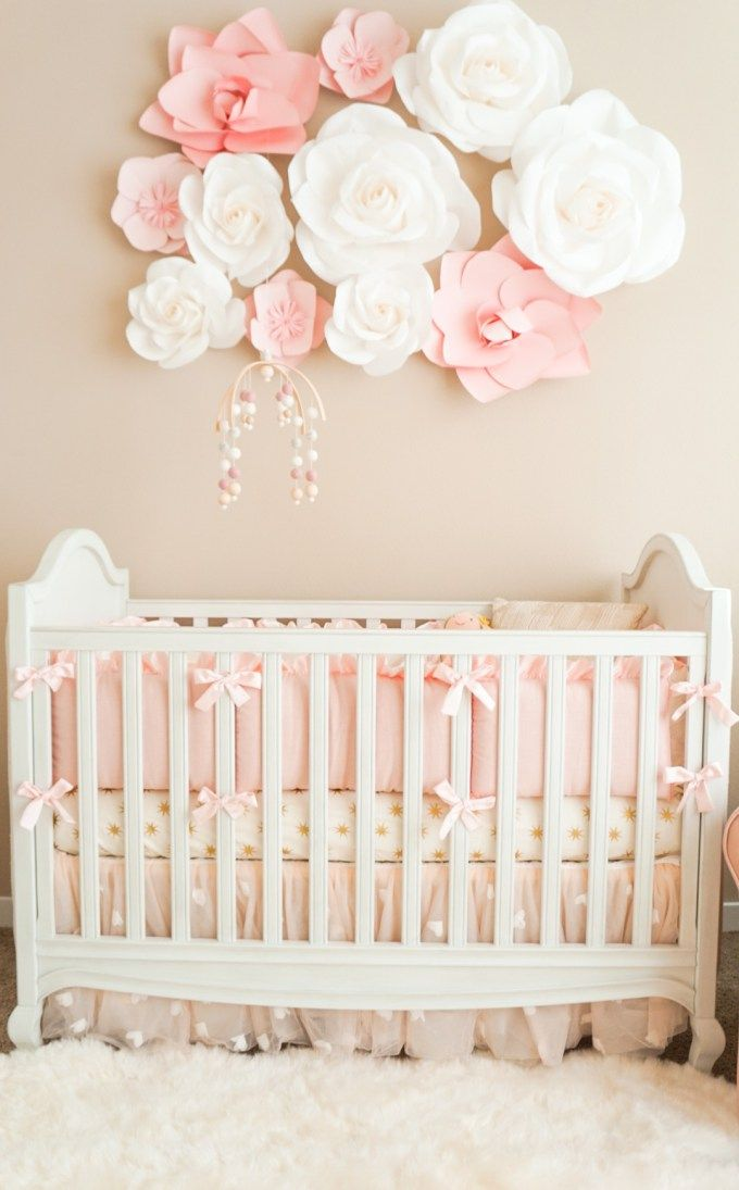 Your new bundle of joy will feel like the princess she is with this pink and cream girl's nursery design. From the bold floral wall decoration to the adorable pink bows on the crib, every detail of this bedroom will help you feel ready to welcome your new baby home.