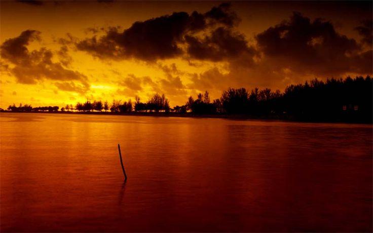 Tijdens uw verblijf in de jungle van het Gunung Mulu National Park op Borneo, Maleisië kunt u bij de rivier genieten van het uitzicht op de ondergaande zon