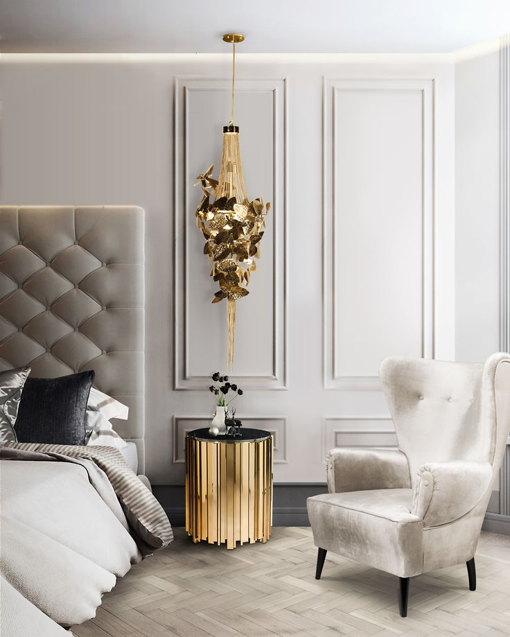 In this sophisticated bedroom light wooden flooring is combined with classic white walls and beige velvet upholstery. Statement furnishings include a cylindrical brass sidetable and a Swarovski Crystal pendant light, both in gold-plated finishes. The result is a fine balance between neutral contemporary and luxury design.