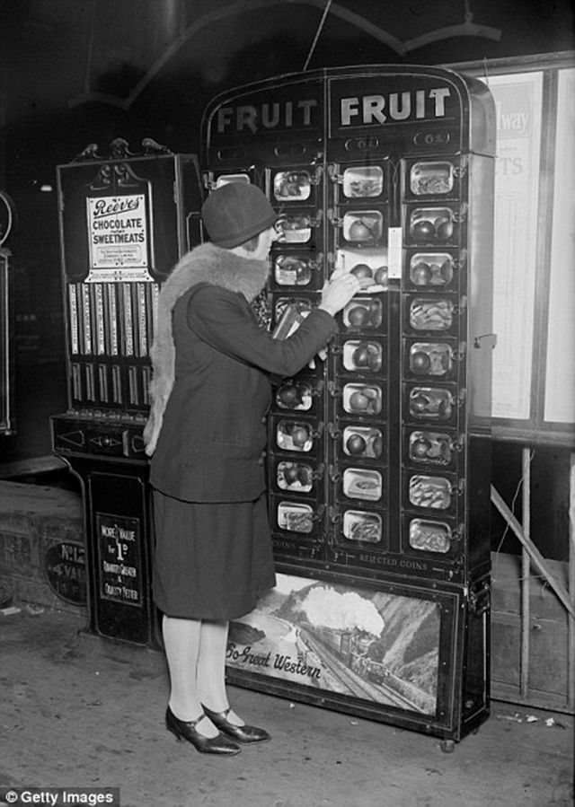 A woman buys fruit from a coin operated machine at Paddington Station in London, ca. 1920s.