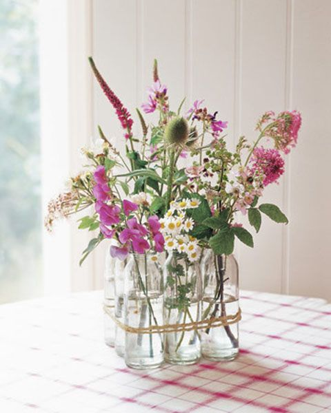 "From ""Country Living"".  Vintage bottles, twine, and wildflowers – beautiful."
