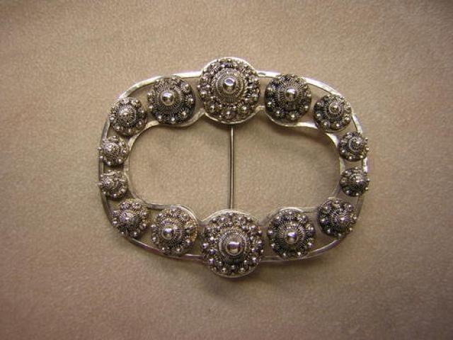 gesp met Zeeuwse knopjes: Zilveren gesp versierd met Zeeuwse knopjes. Dit soort gesp werd in diverse delen van Zeeland op de schort of japon gedragen. Ook buiten de provincie kwam dit voor bij de algemene mode van die tijd  (ca.1900.)
