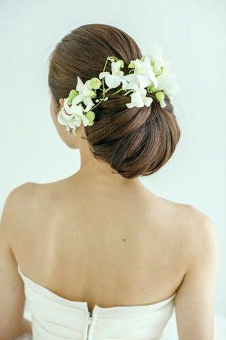 ヘッドコサージュは、シニヨンを囲むように、また前からも見えるように飾るとさわやかさがアップ。 ウェディングドレス・カラードレスに合う〜シニヨンの花嫁衣装の髪型まとめ一覧〜