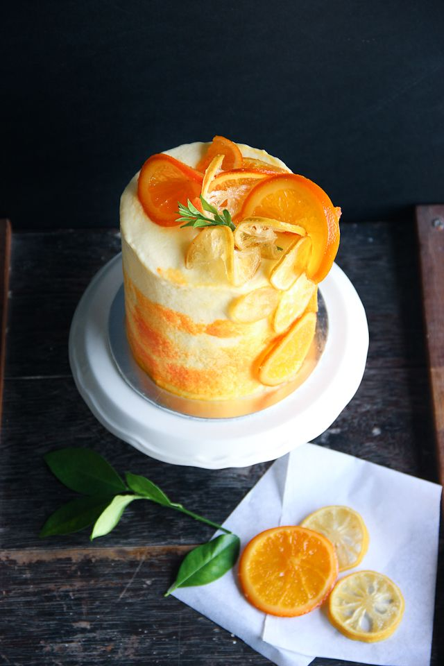 Lemon cake filled with tangy lemon curd, frosted with lemon buttercream and decorated with candied lemon and orange slices. The sunrise gave me inspiration for this cake. -The Bake Idea by Tsuqi