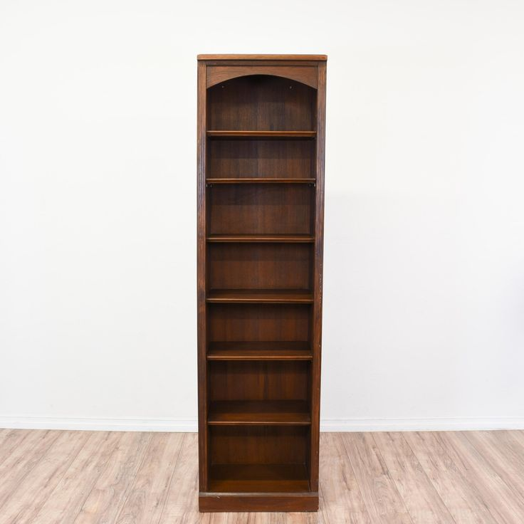 This tall and narrow bookcase is featured in a solid wood with a rustic dark oak finish. This bookshelf is in great condition with 6 shelf tiers, a curved top and carved trim. Perfect for displaying books or dvds! #traditional #storage #bookcase&shelving #sandiegovintage #vintagefurniture