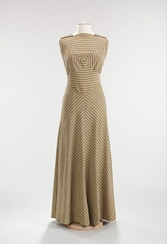 The artful piecing of the fabric in this dress creates an interesting visual effect, drawing the eyes from the metallic braid shoulder straps with gold-tone ball button accents, to the center of the bodice where the pieces intersect, creating squares radiating out to the edges. The waistline is accentuated with two center points, one leading into the CF seam of the skirt, which is pieced to create a chevron pattern. This method of piecing is a precursor to work by such designers as Gilbert…