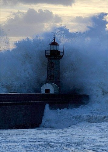 Heavy seas and waves crash over a lighthouse at Douro's River mouth in Porto, Portugal.