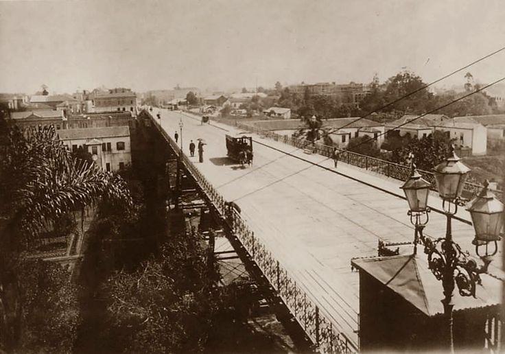 1896 - Antigo Viaduto do Chá. Sob o viaduto temos plantações de chá e o ribeirão Anhangabaú. Podemos ver em ambos os lados do viaduto as casas de aluguel de propriedade do Barão de Itapetininga.