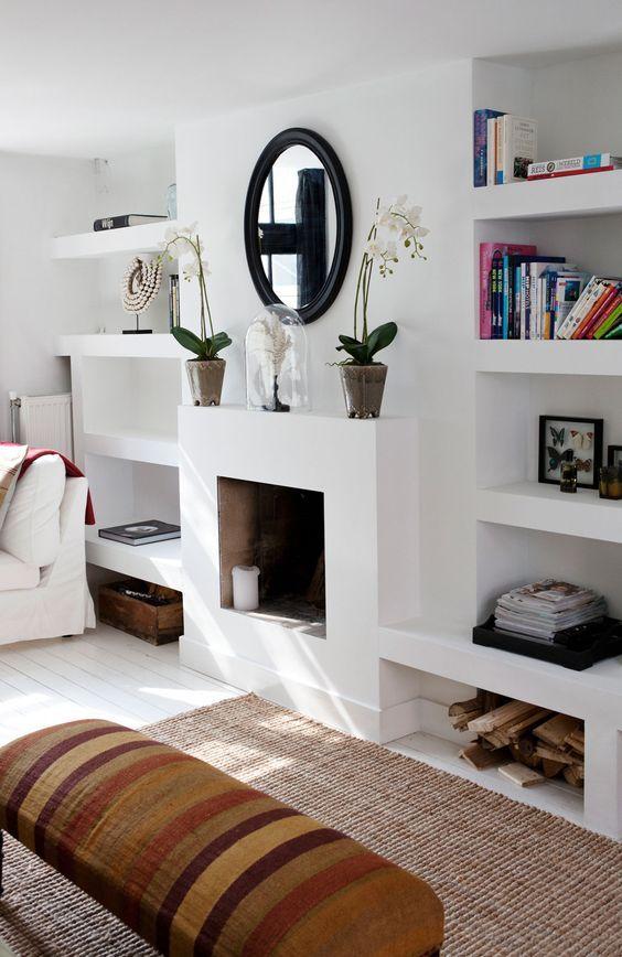 Piccolo camino perfettamente integrato all'interno della libreria in cartongesso. Stile molto elegante total white