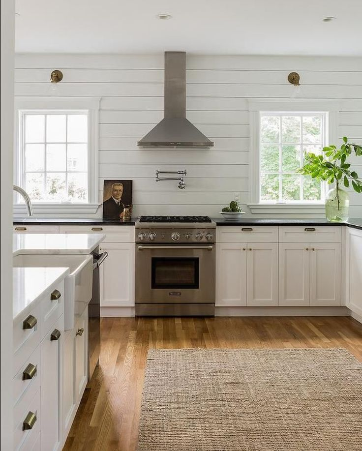 Shiplap walls, white cabinetry, honed absolute black granite, antique brass cup pulls