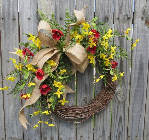 This beautiful red and yellow wreath is characterized by realistic forsythia, poppies, and fern. A wired burlap ribbon makes a simple bow. Average