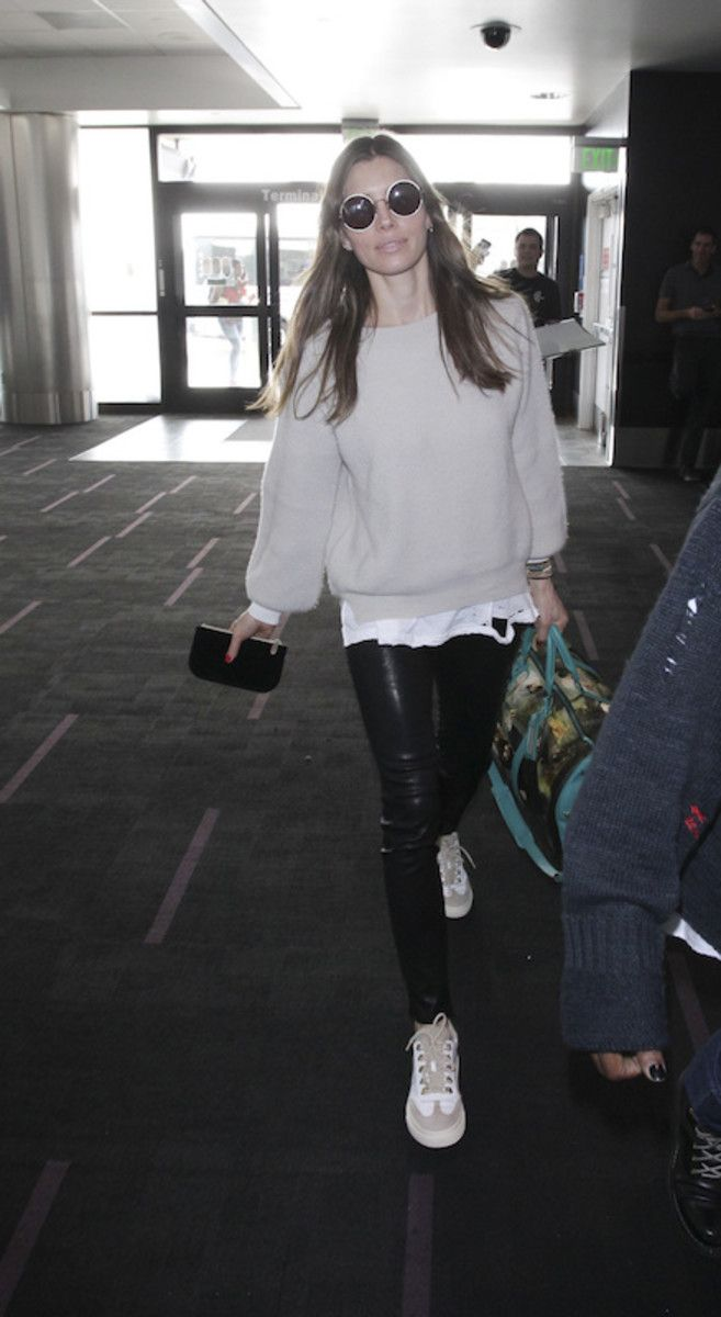 Jessica Biel wearing a light beige balloon sleeve sweater, white distressed t-shirt, black leather skinny pants, round oversized sunglasses, and two tone sneakers