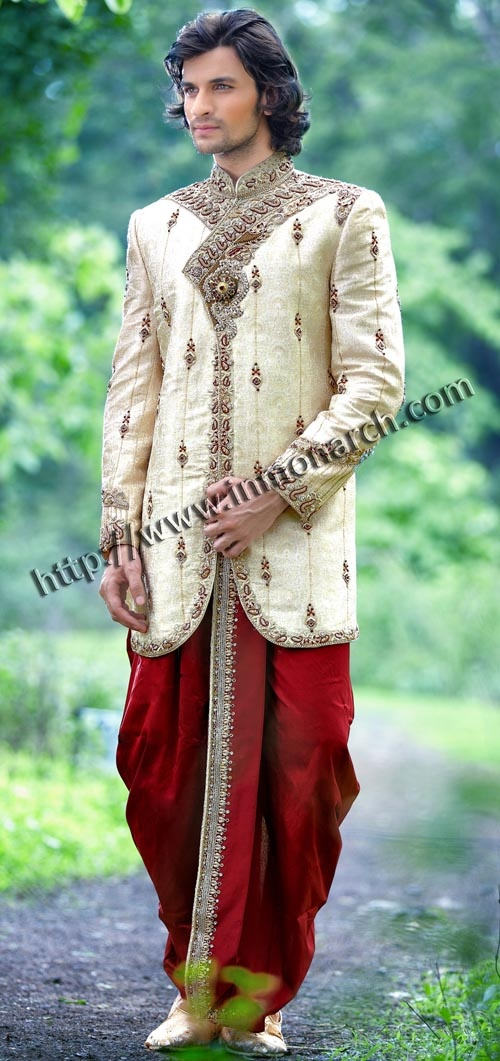Dazzling embroidered wedding sherwani made from cream color brocade fabric. Hand embroidered as shown. It has bottom as dhoti made from dupion fabric in red color.