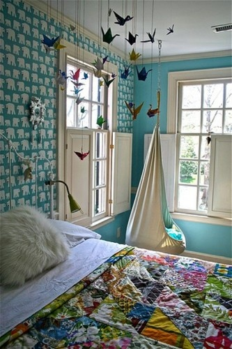The oragami crane mobile in this room is one of a kind and matches the colorful bed spread.