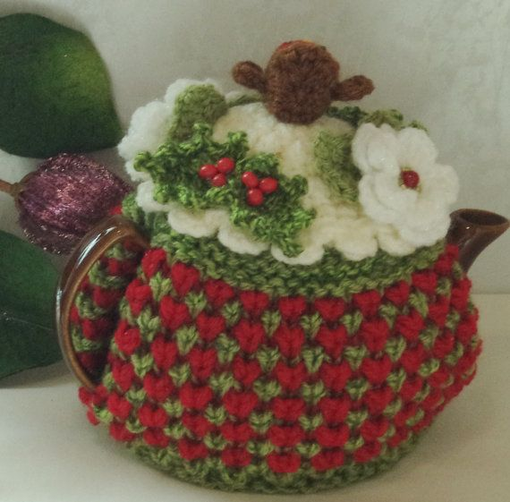 a one of a kind Christmas tea cosy with robin, Christmas roses and holly ...knitted in with soft red, green and cream chunky wool with a cream crochet top and scallop edge..... ...soft and thick to keep tea nice and hot....  this cosy fits a standard, round 2 cup tea pot and measures just over 13 inches by over 6 inches....to the top of the little robin....  the robin in crocheted in red and brown wool with a yellow yarn beak and black wool eyes....  he is surrounded by 2 dark green knitted…