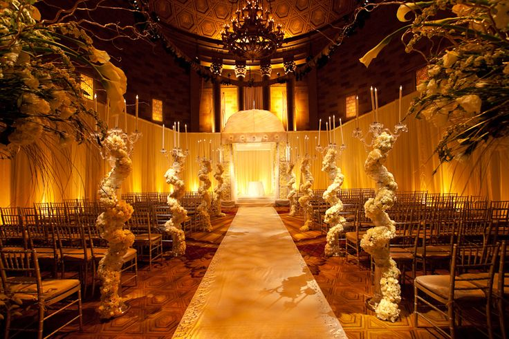 extravagant candelabras  and dramatic arrangements line this aisle