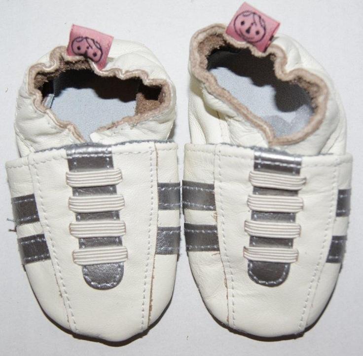 Sportieve witte leren babyslofjes met grijze strepen.