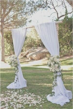 Tie white curtains with floral arrangements on wooden frame ...for budget friendly outdoor wedding platform