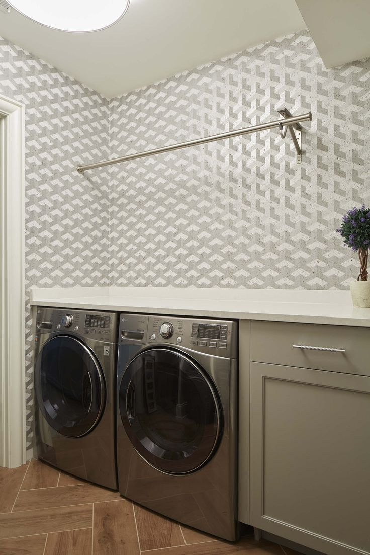 """Morgante Wilson disigned a fun yet functional laundry room space to spend time in. The """"cubism"""" pattern and grey/white/metallic colorway combined with the cork material adds an interesting aesthetic to the room. The wallpaper was purchased from Innovations."""