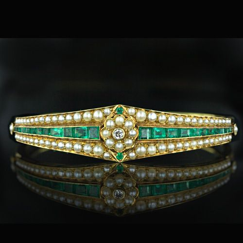 A tailored late Victorian bangle bracelet, crafted in 14 karat yellow gold, is fully set with emeralds, natural seed pearls and a single diamond. The calibre cut emeralds are channel set and slightly graduate towards the center with a charming seed pearl and diamond floral motif. For an elegant lady.