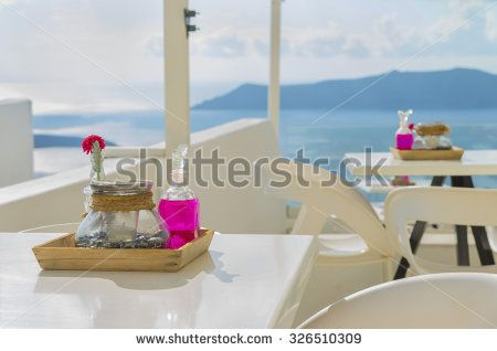Candleholder, vase with flower and glass jar with pink liquid on the tray.Beautiful decoration of tables in the restaurant above the caldera in a marine style. Santorini(Thira)island.Cyclades.Greece.
