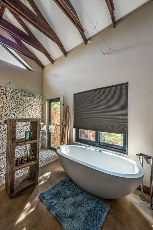 The stone wall and freestanding bath somehow matching up beautifully in this bathroom by olivehill architects