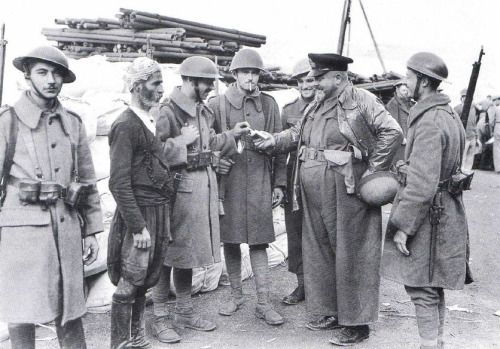 Greek soldiers mingle with a local civilian on Crete prior to the German invasion of the island. May, 1941