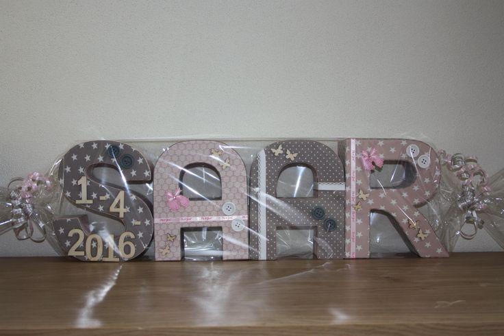 Kartonnen letters, gedecoreerd met o.a. stofjes, lintjes en knoopjes. Geboortedatum in houten cijfers. Leuk om cadeau te geven bij verjaardag of geboorte.