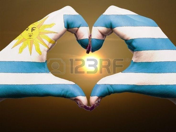 Turismo de Uruguay hizo por América manos la bandera de colores que muestran el símbolo del corazón y el amor durante el amanecer Foto de archivo