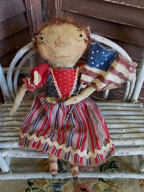 "11"" tall Raggedy Ann is ready for summer and Independence Day! She wears a dress made from different red, white and blue fabrics. It was trimmed with white ric rac and wears red bloomers underneath.  She has a hand stitched face and auburn hair and has been firmly stuffed with rags for a great old fashioned look. Lastly, she brought her 5"" tall handmade flag to wave as the parade goes by. Twig holds Old Glory up high.  It has been signed/dated as an original, one of a kind collectible de..."