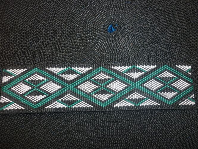 This is a taniko band of green, white and black. I really like the colours because they all match and go together really well and you can see the vertical diamond shapes going through. It is nicely stitched and the black outline really stands out really well.
