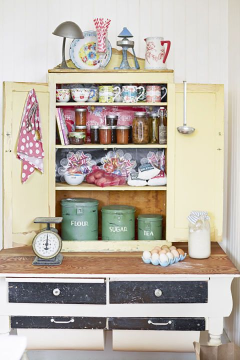 Baking Cupboard:  The owner of this California home bakes with her daughters every week, and they store their canned jams, baking supplies, and darling cups in this dusty yellow cabinet, which is decorated with farmhouse antiques.