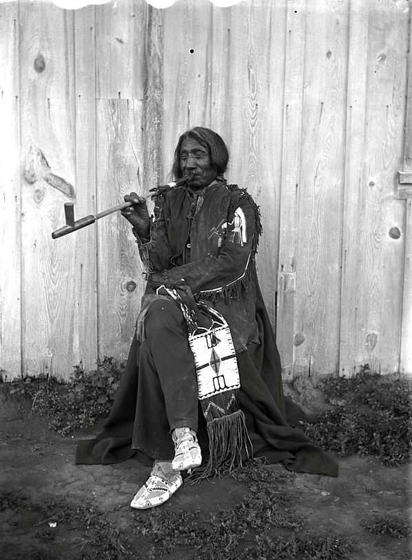 Sioux Chief Red Cloud and pipe. 1898. South Dakota. Rosebud Reservation. Photo by Jesse H. Bratley. —