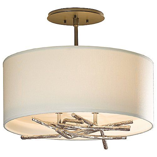 """The Hubbardton Forge Brindille Aluminum Semi Flushmount derives its name from the French word for twig. Underneath a simple drum shade, is an organically arranged pile of hand forged """"twigs"""". This mixture of materials found in nature against a standard shade offers an interesting juxtaposition of shapes and color schemes."""