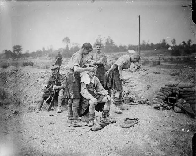 A barber at the Black Watch during the somme - WW1 - 1916. Photo b/w, soldiers, cutting hair, history.