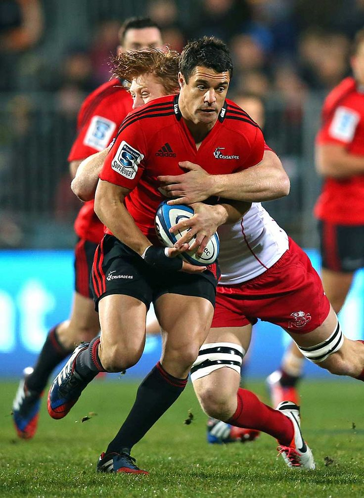 The Crusaders' Dan Carter breaks a tackle from the Reds' Ed Quirk