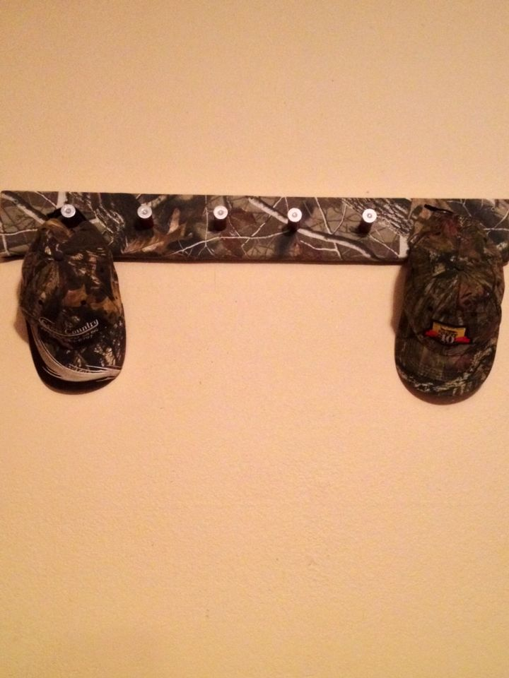 Diy shot Gun shell cap rack . I made .with wood camo fabric, empty shot gun shells !! Eazy and my Husband loves it!