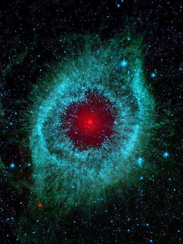 Nebulosa de la Hélice. Esta imagen, capturada por el telescopio espacial Spitzer, muestra la enorme concentración de polvo en el centro de la nebulosa, reflejándola con un intenso color rojo.