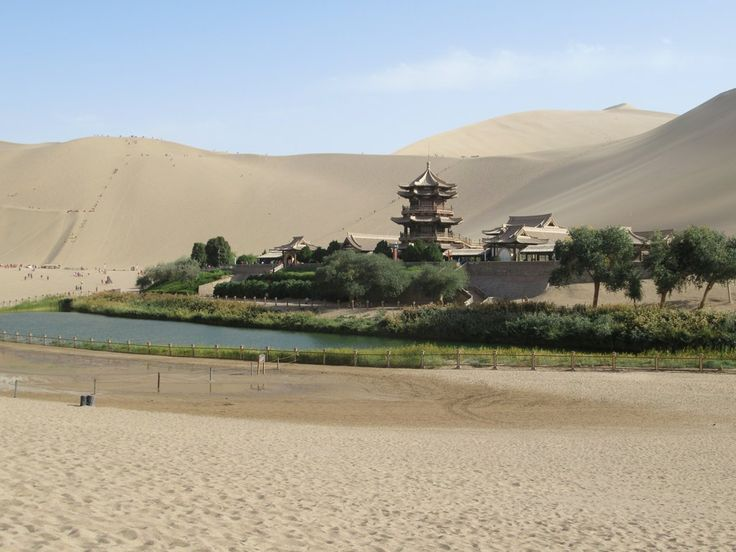 The Mingsha Sand Dunes rise above Crescent Lake just south of Dunhuang, Gansu, China. Marco Polo refered to these `rumbling sands` which `sing` as the wind blows over them.