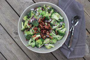 Broccolisalat    Opskrift Recept Broccolisallad: 2 broccoli, små buketter  2 rødløg (tern) 1 pakke bacon i tern 1 lille håndfuld rosiner 1 lille håndfuld solsikkekerner 2-3 dl créme fraîche, skyr, kvarg  2 spsk mayo Saften fra 1 citron 2 spsk sukker/sukrin Salt og peber