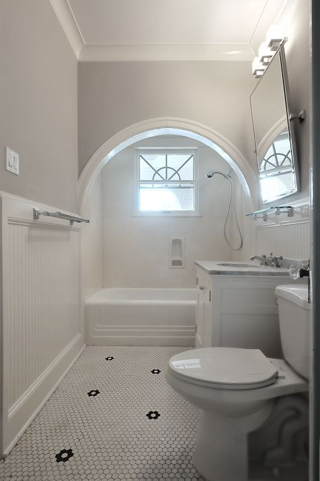 White and gray bathroom features an arched alcove filled