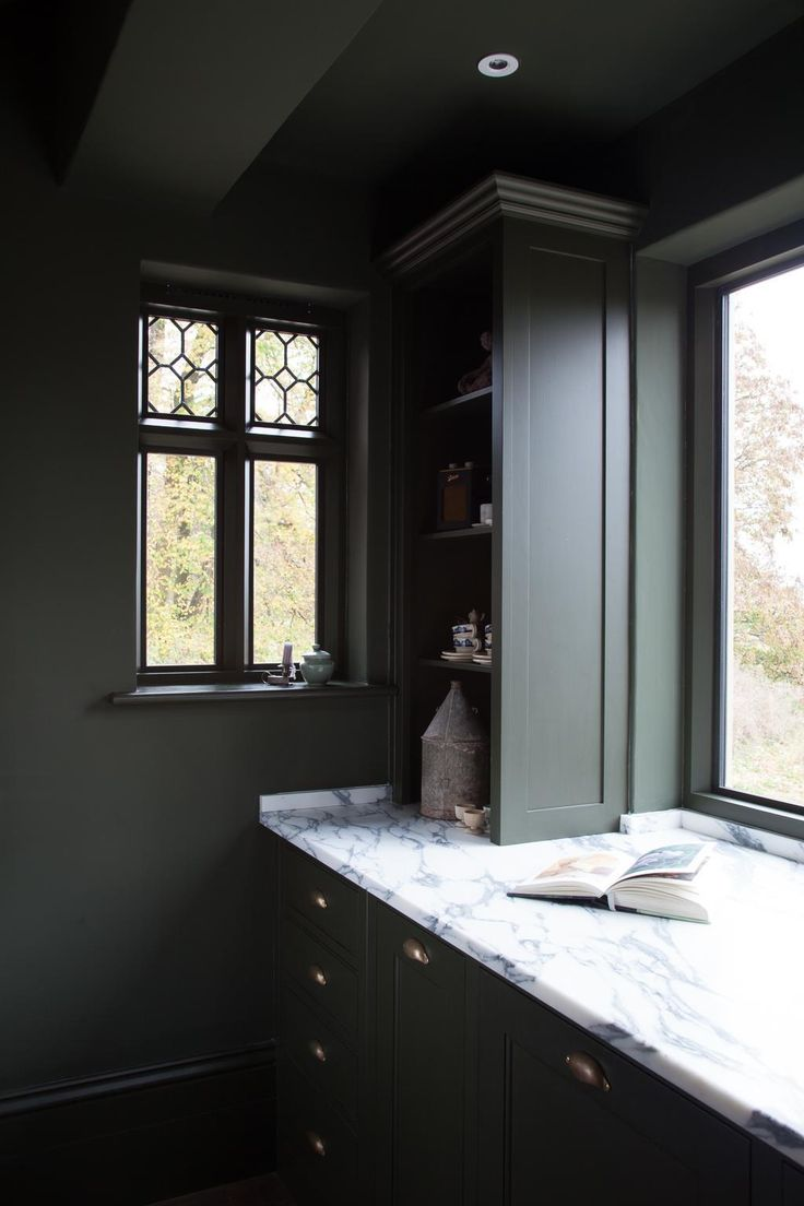 Dark green kitchen cabinets with marble countertops by Plain English.