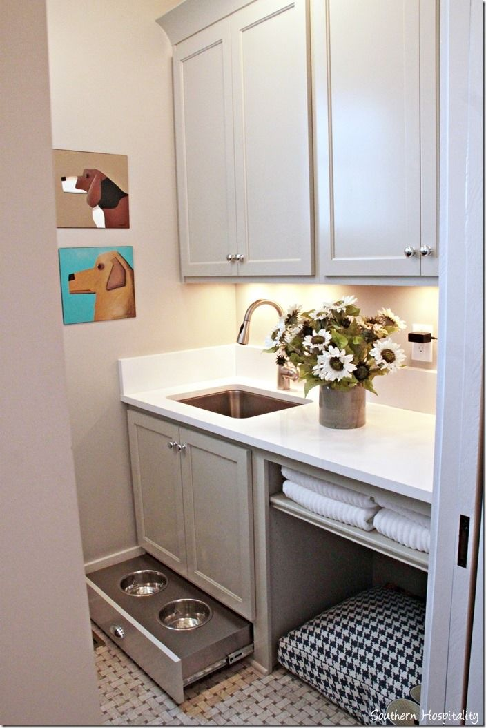 Laundry room with pullout doggy feeding trays. Love the dog pictures too!