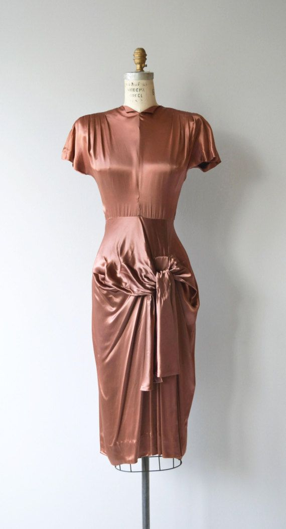 vintage 1940s bronze silk dress with high neck, dramatic silhouette with small shoulder pads, fitted waist and hip swag. Metal back zipper. --- M E A S U R E M E N T S ---  fits like: xs/small bust: 35 waist: 25 hip: 38 length: 46 brand/maker: Young Hollywood condition: very good, one small mark on the back of the skirt (pictured) and a few minor snags.  to ensure a good fit, please read the sizing guide: http://www.etsy.com/shop/DearGolden/po...