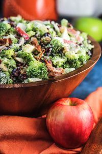 Fall flavors come alive in this Broccoli Cranberry Salad with Apples, Bacon and Walnuts! Broccoli, cranberries, diced apples, bacon and walnuts are tossed with a creamy and sweet maple dressing. Serve cold!